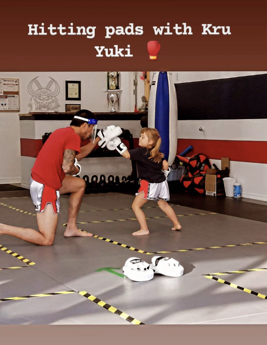 Kru Yuki and one of our little nak muays hitting pads while wearing PPE